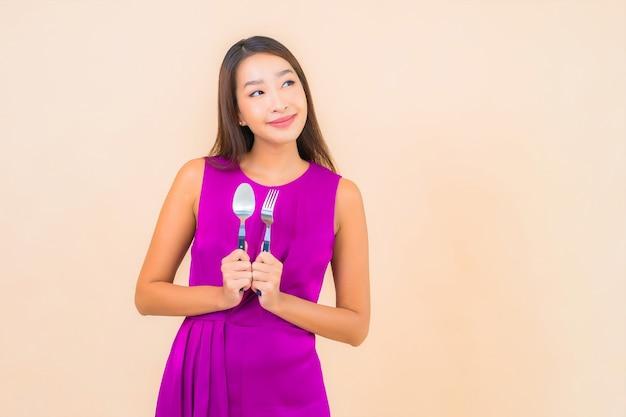 Porträt schöne junge asiatische frau mit gabel und löffel bereit zu essen auf farbhintergrund Kostenlose Fotos