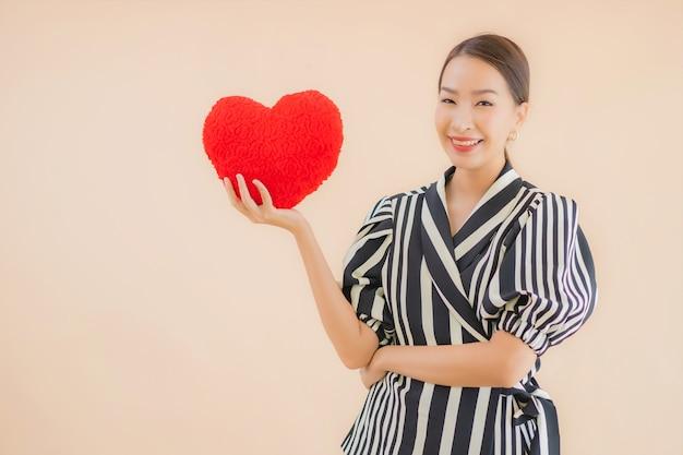 Porträt schöne junge asiatische frau mit herzkissen Kostenlose Fotos