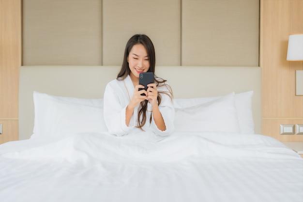 Porträt schöne junge asiatische frau mit intelligentem handy im schlafzimmer Kostenlose Fotos