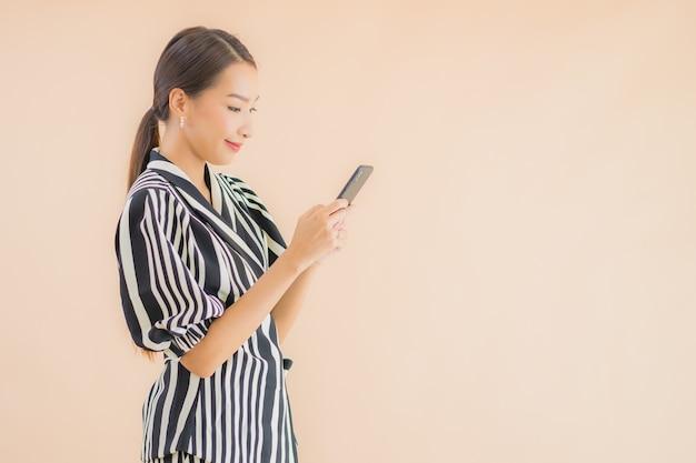 Porträt schöne junge asiatische frau mit intelligentem handy Kostenlose Fotos