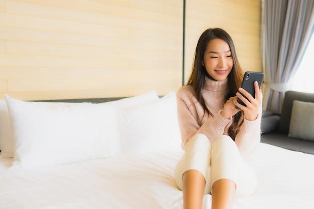 Porträt schöne junge asiatische frau mit kaffeetasse und handy auf dem bett Kostenlose Fotos