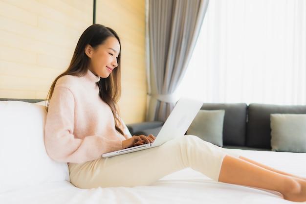 Porträt schöne junge asiatische frau mit laptop mit handy auf dem bett Kostenlose Fotos