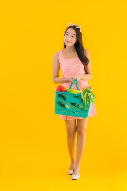 Porträt schöne junge asiatische frau mit lebensmittelgeschäft im korb einkaufen vom supermarkt Kostenlose Fotos