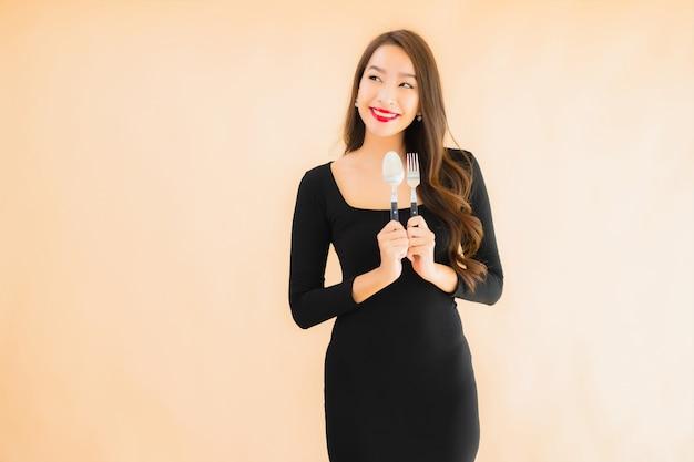 Porträt schöne junge asiatische frau mit löffel und gabel Kostenlose Fotos
