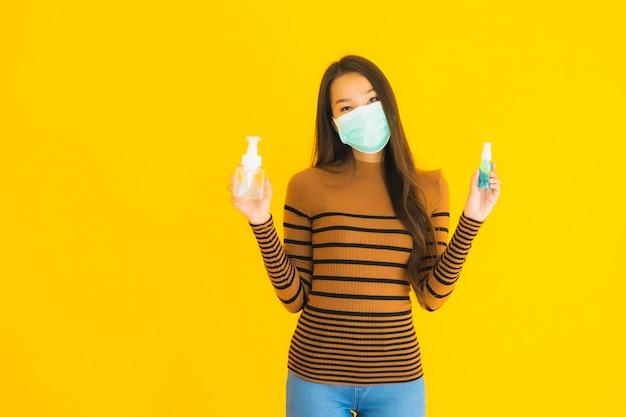 Porträt schöne junge asiatische frau mit maske alkoholspray und gelflasche in der hand zum schutz vor coronavirus oder covid19 Kostenlose Fotos