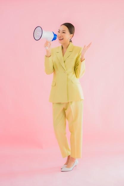 Porträt schöne junge asiatische frau mit megaphon auf farbe Kostenlose Fotos