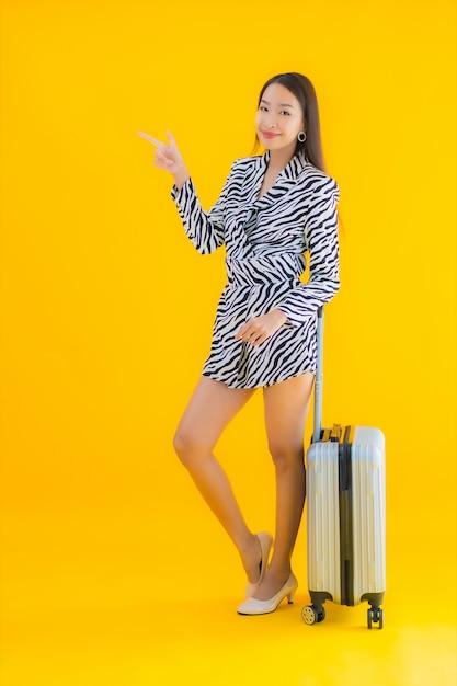 Porträt schöne junge asiatische frau mit reisegepäckpass und bordkarte auf gelb Kostenlose Fotos