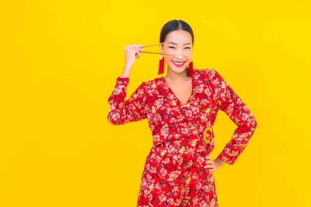 Porträt schöne junge asiatische frau mit stäbchen auf farbe isolierte wand Kostenlose Fotos