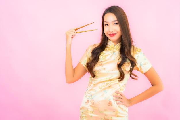 Porträt schöne junge asiatische frau mit stäbchen auf rosa wand Kostenlose Fotos