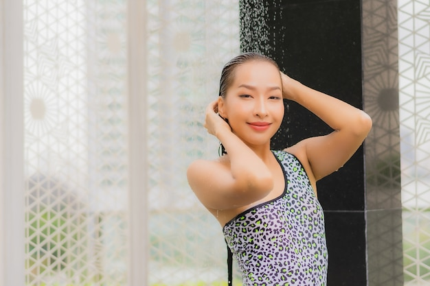 Porträt schöne junge asiatische frau nehmen eine dusche um außenpool Kostenlose Fotos
