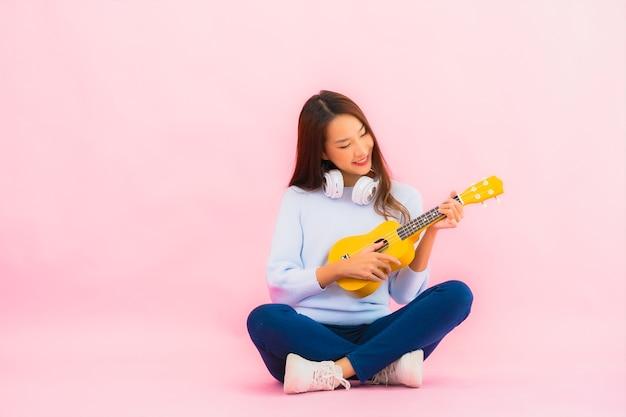 Porträt schöne junge asiatische frau spielen ukulele auf rosa farbe isolierte wand Kostenlose Fotos