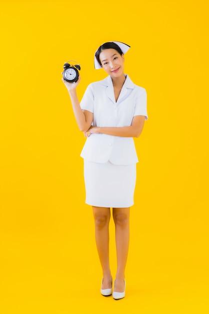Porträt schöne junge asiatische frau thailändische krankenschwester mit uhr oder alarm Kostenlose Fotos