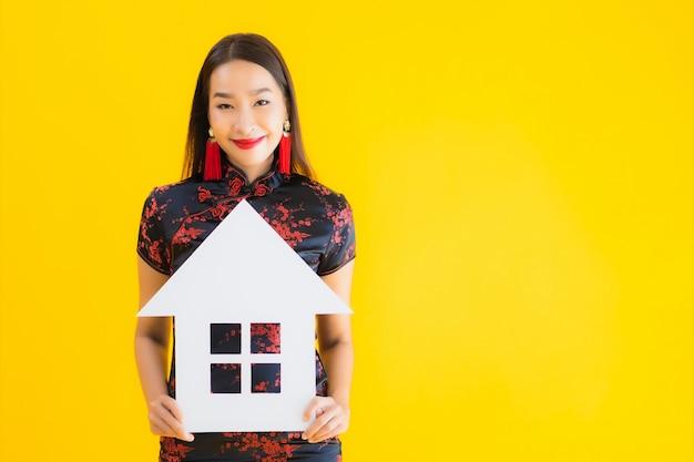 Porträt schöne junge asiatische frau tragen chinesisches kleid zeigen hauszeichen Kostenlose Fotos