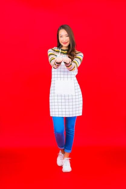 Porträt schöne junge asiatische frau tragen schürze an der roten wand Kostenlose Fotos