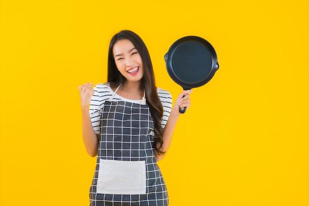 Porträt schöne junge asiatische frau tragen schürze mit schwarzer pfanne und spatel Kostenlose Fotos