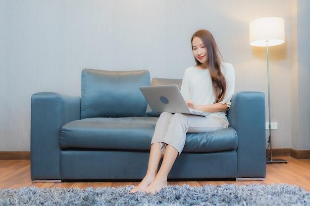 Porträt schöne junge asiatische frau verwenden computer laptop auf sofa im wohnzimmer interieur Kostenlose Fotos