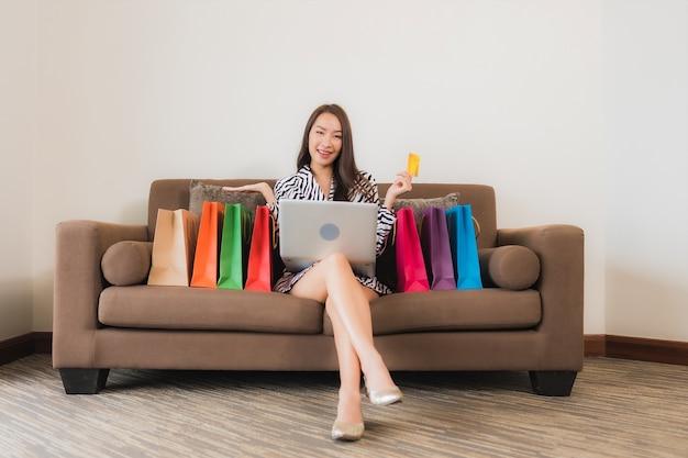 Porträt schöne junge asiatische frau verwenden computer-laptop, smartphone oder bargeld für online-shopping auf sofa im wohnzimmer interieur Kostenlose Fotos