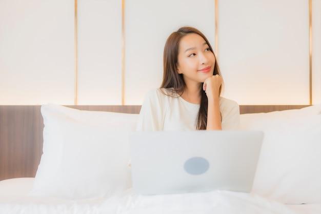 Porträt schöne junge asiatische frau verwenden laptop auf bett im schlafzimmer interieur Kostenlose Fotos