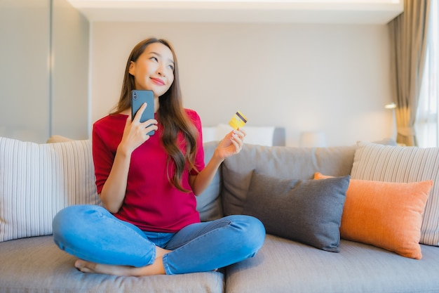Porträt schöne junge asiatische frau verwenden smartphone mit kreditkarte Kostenlose Fotos