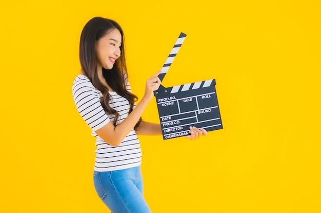 Porträt schöne junge asiatische frau zeigen klöppel filmbrett Kostenlose Fotos