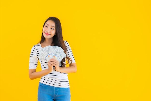 Porträt schöne junge asiatische frau zeigen viel dollar bargeld oder geld Kostenlose Fotos