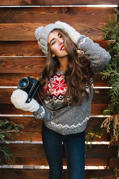 Porträt schönes mädchen mit langen haaren in strickmütze und handschuhen halten kamera auf holz. sie lächelt . Kostenlose Fotos