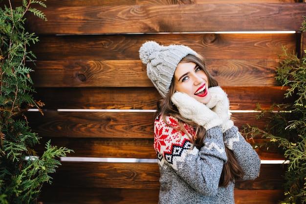 Porträt schönes mädchen mit langen haaren in strickmütze und winterpullover auf holz. sie berührte das gesicht mit händen in handschuhen und lächelte. Kostenlose Fotos