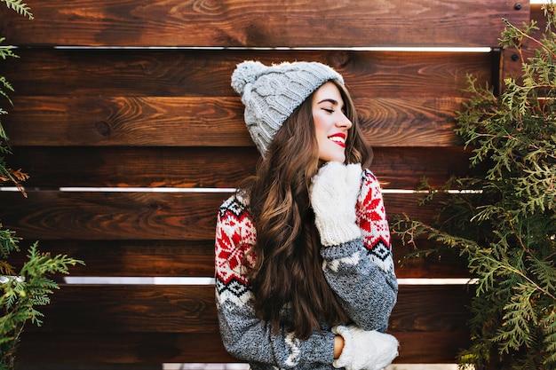 Porträt schönes mädchen mit langen haaren und roten lippen in der warmen winterkleidung auf holz. sie lächelt zur seite und hält die augen geschlossen. Kostenlose Fotos