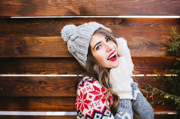Porträt schönes mädchen mit langen haaren und roten lippen in strickmütze und handschuhen auf holz. sie lächelt . Kostenlose Fotos