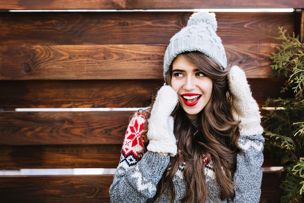 Porträt schönes mädchen mit langen haaren und roten lippen in strickmütze und warmen handschuhen auf holz. sie lächelte zur seite. Kostenlose Fotos