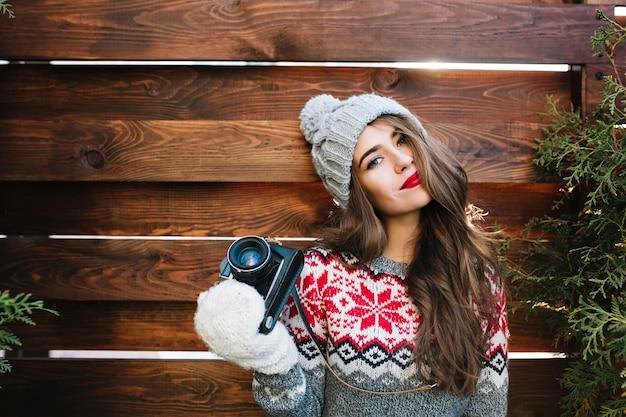 Porträt schönes mädchen mit roten lippen in strickmütze und handschuhen, die kamera auf holz halten. Kostenlose Fotos