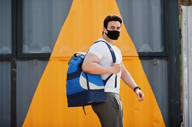 Porträt sportlicher arabischer mann in der schwarzen medizinischen gesichtsmaske mit rucksack, der gegen gelbes dreieck während der coronavirus-quarantäne gestellt wird. Premium Fotos