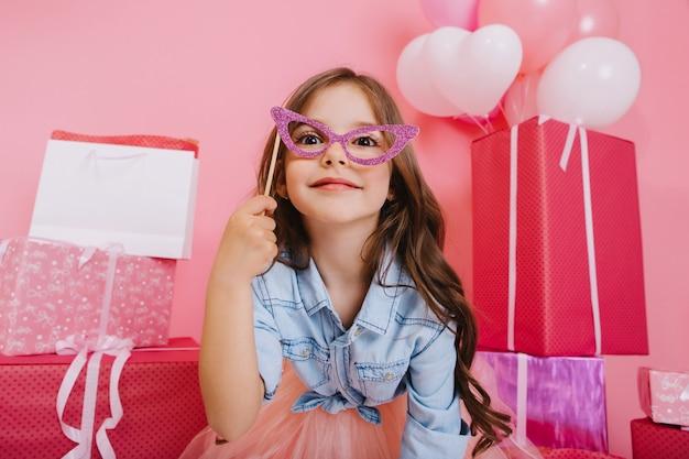 Porträt süßes kleines mädchen mit langen brünetten haaren, die maske auf gesicht halten, kamera auf geschenkboxen, luftballons, rosa hintergrund schauend. schönes aufgeregtes kind, das spaß hat und geburtstagsfeier feiert Kostenlose Fotos