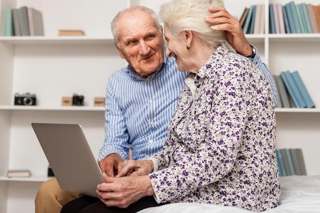 Porträt von älteren paaren unter verwendung eines laptops Kostenlose Fotos