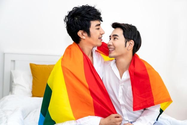 Porträt von asiatischen homosexuellen paaren umarmen und hand mit stolzflagge im schlafzimmer halten konzept lgbt-homosexuelles. Premium Fotos