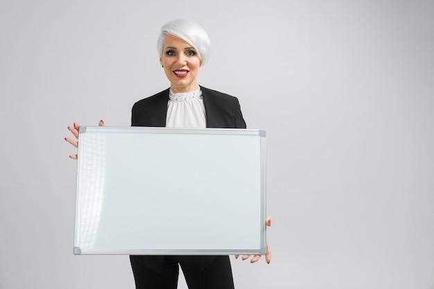 Porträt von blondinen eine magnettafel in ihren händen halten an lokalisiert Premium Fotos