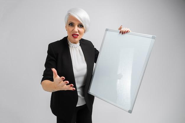 Porträt von blondinen eine magnettafel in ihren händen halten lokalisiert auf hintergrund Premium Fotos