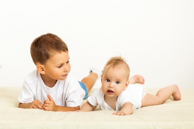 Porträt von bruder und schwester. zwei süße kinder, die auf bett liegen Premium Fotos