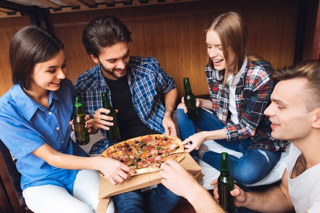 Porträt von den freunden, die sich zusammen entspannen, essen pizza Premium Fotos