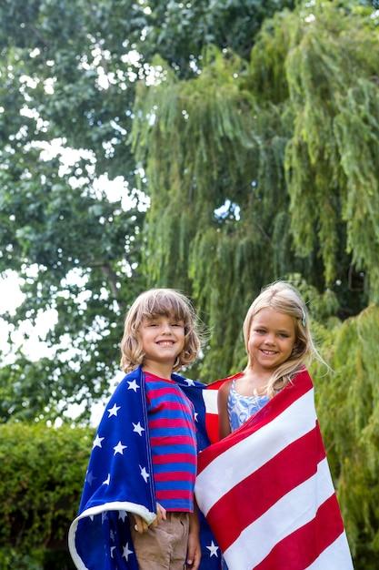Porträt von den geschwistern, die in der amerikanischen flagge am hinterhof eingewickelt werden Premium Fotos
