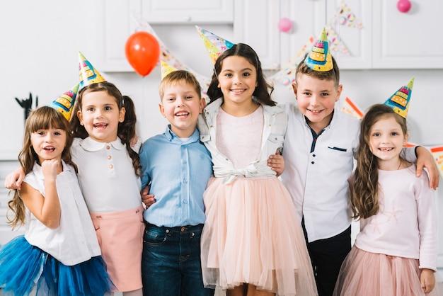 Porträt von den glücklichen freunden, die den partyhut tragen zusammen stehen Kostenlose Fotos
