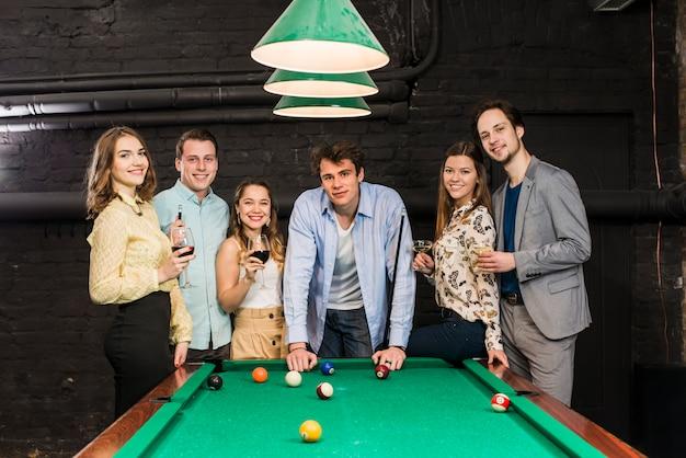 Porträt von den glücklichen freunden, die hinter der snookertabelle genießen, im club genießend Kostenlose Fotos