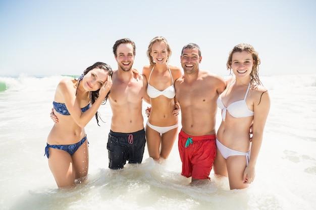 Porträt von den glücklichen freunden, die zusammen auf dem strand stehen Premium Fotos