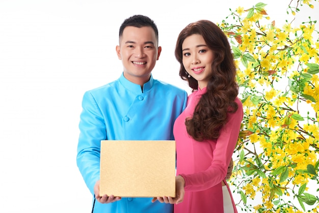 Porträt von den jungen asiatischen paaren, die eine geschenkbox zusammenhalten Kostenlose Fotos
