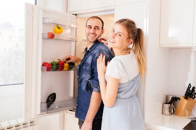 Porträt von den jungen paaren, die vor einem offenen kühlschrank mit gemüse stehen Kostenlose Fotos
