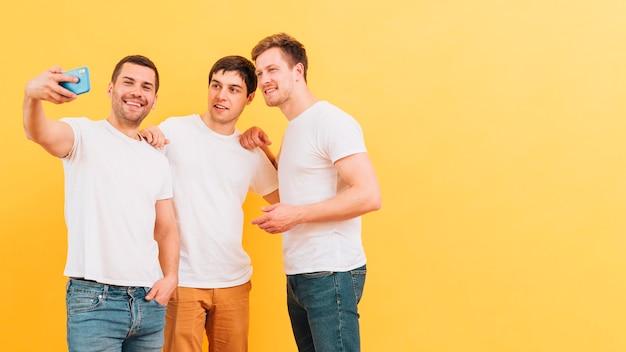 Porträt von den lächelnden jungen männlichen freunden, die selfie am intelligenten telefon gegen gelben hintergrund nehmen Kostenlose Fotos