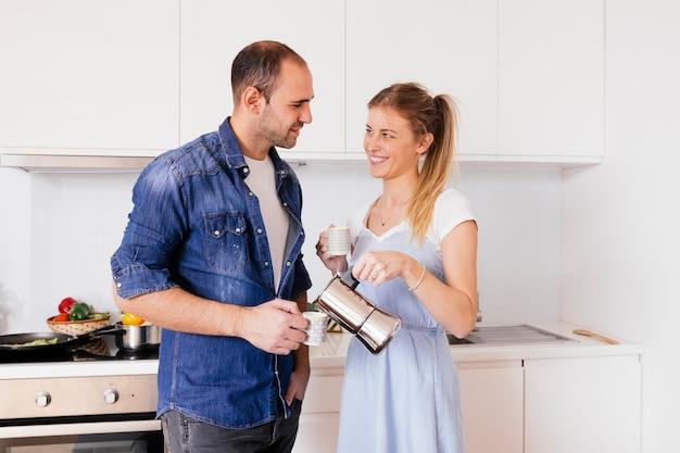 Porträt von den lächelnden jungen paaren, die den kaffee stehen in der küche trinken Kostenlose Fotos