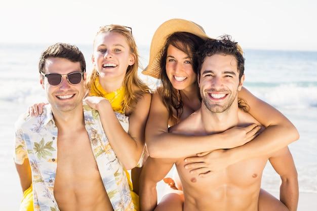 Porträt von den männern, die den frauen auf dem strand ein doppelpol geben Premium Fotos