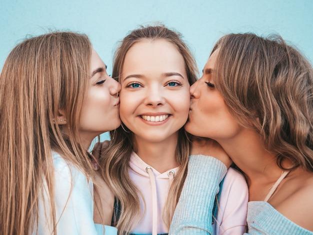 Porträt von den sexy sorglosen frauen, die in der straße aufwerfen positive modelle, die ihren freund in der backe küssen Kostenlose Fotos