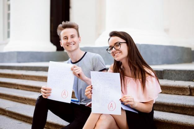 Porträt von den studenten, die auf treppe sitzen und perfekte testergebnisse zeigen. Premium Fotos